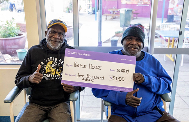 Clients of Purple House receiving cheque from MAX Foundation